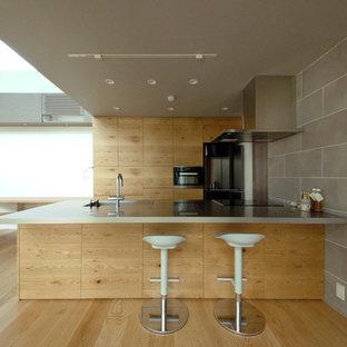 東京23区のモダンスタイルのおしゃれなキッチン (シングルシンク、フラットパネル扉のキャビネット、中間色木目調キャビネット、ステンレスカウンター、無垢フローリング、茶色い床) の写真