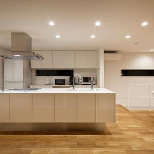 他の地域のモダンスタイルのおしゃれなキッチン (茶色い床、白いキッチンカウンター) の写真