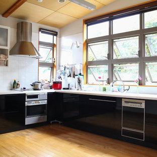 他の地域の大きいモダンスタイルのおしゃれなキッチン (黒いキャビネット、白いキッチンパネル、白いキッチンカウンター) の写真