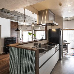 他の地域のインダストリアルスタイルのおしゃれなキッチン (シングルシンク、フラットパネル扉のキャビネット、白いキャビネット、ステンレスカウンター、白いキッチンパネル、黒い調理設備) の写真