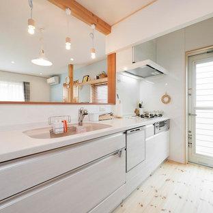 他の地域のカントリー風おしゃれなキッチン (一体型シンク、フラットパネル扉のキャビネット、白いキャビネット、淡色無垢フローリング、茶色い床) の写真