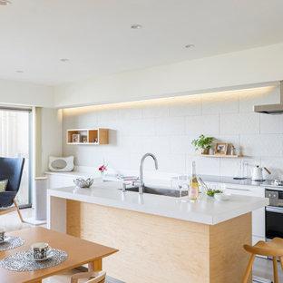 他の地域のコンテンポラリースタイルのおしゃれなキッチン (アンダーカウンターシンク、フラットパネル扉のキャビネット、白いキャビネット、白いキッチンパネル、シルバーの調理設備、グレーの床、グレーのキッチンカウンター) の写真