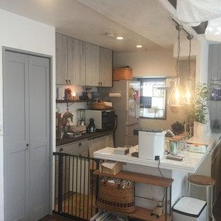 福岡の小さいシャビーシック調のおしゃれなキッチン (シングルシンク、グレーのキャビネット、人工大理石カウンター、磁器タイルのキッチンパネル、シルバーの調理設備、トラバーチンの床、ベージュの床、白いキッチンカウンター) の写真