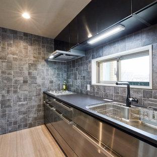 他の地域の小さいインダストリアルスタイルのおしゃれなII型キッチン (アンダーカウンターシンク、フラットパネル扉のキャビネット、ステンレスキャビネット、グレーのキッチンパネル、磁器タイルのキッチンパネル、シルバーの調理設備、アイランドなし、ベージュの床、黒いキッチンカウンター) の写真