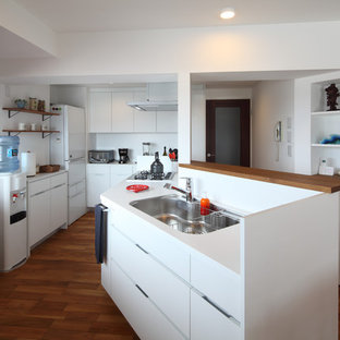 他の地域のビーチスタイルのおしゃれなキッチン (フラットパネル扉のキャビネット、白いキャビネット、人工大理石カウンター、白いキッチンパネル、シルバーの調理設備、無垢フローリング、茶色い床、シングルシンク) の写真