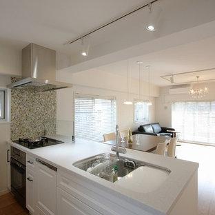 東京23区のコンテンポラリースタイルのおしゃれなアイランドキッチン (シングルシンク、落し込みパネル扉のキャビネット、白いキャビネット、茶色い床) の写真
