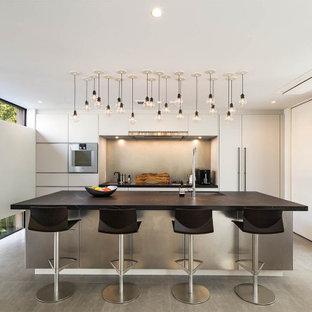 コンテンポラリースタイルのおしゃれなキッチン (アンダーカウンターシンク、白いキャビネット、白いキッチンパネル、シルバーの調理設備、グレーの床、マルチカラーのキッチンカウンター) の写真