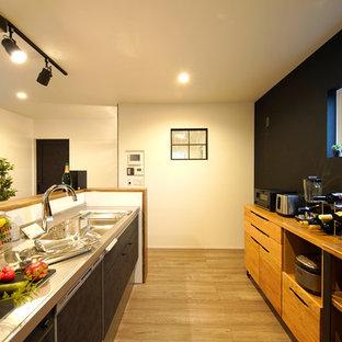 他の地域のインダストリアルスタイルのおしゃれなキッチン (一体型シンク、フラットパネル扉のキャビネット、黒いキャビネット、ステンレスカウンター、無垢フローリング、茶色い床) の写真