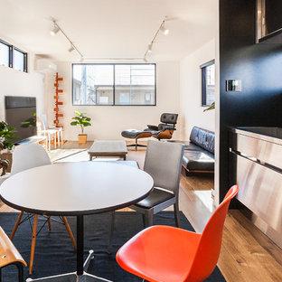 他の地域の小さいコンテンポラリースタイルのおしゃれなアイランドキッチン (シングルシンク、フラットパネル扉のキャビネット、ステンレスキャビネット、ステンレスカウンター、黒いキッチンパネル、無垢フローリング、茶色い床) の写真