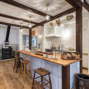 他の地域の中くらいの地中海スタイルのおしゃれなキッチン (シングルシンク、グレーのキャビネット、木材カウンター、白いキッチンパネル、磁器タイルのキッチンパネル、シルバーの調理設備、淡色無垢フローリング、茶色い床、茶色いキッチンカウンター) の写真