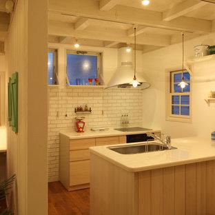Exemple d'une petite cuisine bord de mer avec un évier 1 bac, un placard à porte plane, des portes de placard en bois clair, un sol en bois brun, un îlot central et un sol marron.