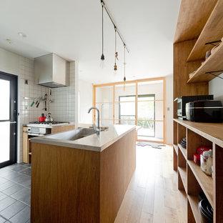 大阪の中サイズのおしゃれなキッチン (アンダーカウンターシンク、ステンレスカウンター、サブウェイタイルのキッチンパネル、グレーの床、茶色いキッチンカウンター) の写真