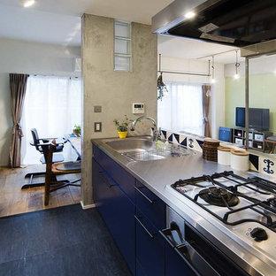 他の地域のインダストリアルスタイルのおしゃれなペニンシュラキッチン (一体型シンク、フラットパネル扉のキャビネット、青いキャビネット、ステンレスカウンター、黒い床) の写真