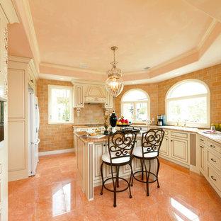 他の地域の地中海スタイルのおしゃれなアイランドキッチン (ドロップインシンク、落し込みパネル扉のキャビネット、白いキャビネット、御影石カウンター、茶色いキッチンパネル、大理石の床、オレンジの床) の写真
