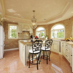 他の地域のヴィクトリアン調のおしゃれなキッチン (ドロップインシンク、落し込みパネル扉のキャビネット、白いキャビネット、御影石カウンター、茶色いキッチンパネル、オレンジの床) の写真