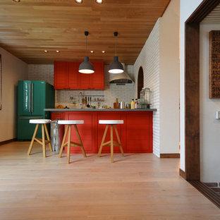 Cette image montre une cuisine ouverte linéaire rustique avec des portes de placard oranges, une crédence orange, un sol en bois clair, un îlot central, un sol blanc et un plan de travail vert.