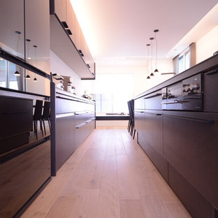 Inspiration for a modern kitchen in Other with flat-panel cabinets, black cabinets, black splashback, black appliances, light hardwood floors and white floor.