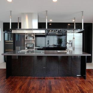 Immagine di una grande cucina moderna con lavello sottopiano, ante lisce, ante nere, top alla veneziana, paraspruzzi con lastra di vetro, elettrodomestici neri, pavimento con piastrelle in ceramica e isola