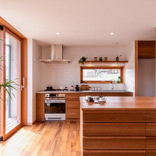 他の地域のアジアンスタイルのおしゃれなキッチン (シングルシンク、落し込みパネル扉のキャビネット、中間色木目調キャビネット、木材カウンター、白いキッチンパネル、無垢フローリング、茶色い床) の写真