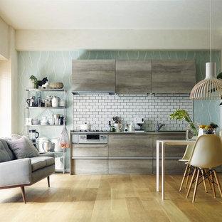 東京23区の北欧スタイルのおしゃれなキッチン (フラットパネル扉のキャビネット、グレーのキャビネット、白いキッチンパネル、セラミックタイルのキッチンパネル、無垢フローリング、茶色い床) の写真