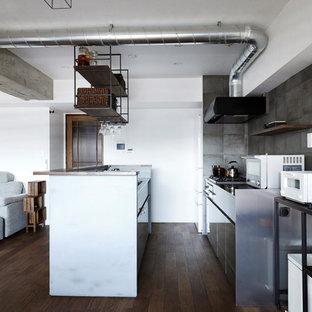 東京23区のアジアンスタイルのおしゃれなキッチン (アンダーカウンターシンク、フラットパネル扉のキャビネット、グレーのキャビネット、グレーのキッチンパネル、白い調理設備、濃色無垢フローリング、茶色い床) の写真