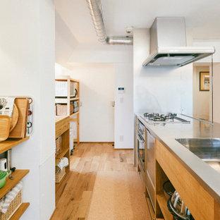 名古屋の広いインダストリアルスタイルのおしゃれなII型キッチン (一体型シンク、フラットパネル扉のキャビネット、中間色木目調キャビネット、ステンレスカウンター、シルバーの調理設備、無垢フローリング、アイランドなし、茶色い床) の写真