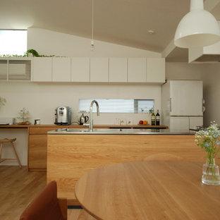 他の地域のコンテンポラリースタイルのおしゃれなLDK (一体型シンク、フラットパネル扉のキャビネット、茶色いキャビネット、ステンレスカウンター、茶色いキッチンパネル、セラミックタイルのキッチンパネル、シルバーの調理設備の、無垢フローリング、茶色い床、茶色いキッチンカウンター) の写真