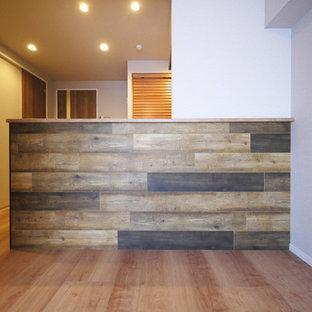 Imagen de cocina lineal, rural, abierta, con puertas de armario de madera oscura, suelo de contrachapado, una isla, suelo marrón y encimeras marrones