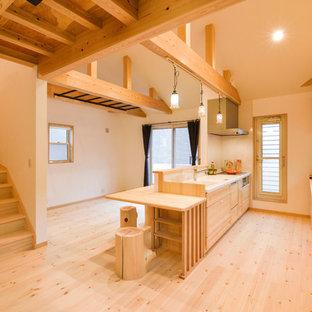 他の地域のカントリー風おしゃれなキッチン (一体型シンク、フラットパネル扉のキャビネット、中間色木目調キャビネット、淡色無垢フローリング、茶色い床) の写真