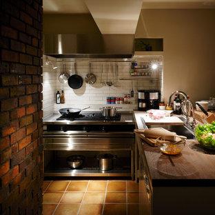東京都下のインダストリアルスタイルのおしゃれなキッチン (木材カウンター、白いキッチンパネル、ボーダータイルのキッチンパネル、シルバーの調理設備の、アイランドなし、ドロップインシンク、テラコッタタイルの床) の写真