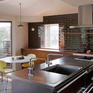 Источник вдохновения для домашнего уюта: маленькая кухня в современном стиле с черным фартуком, обеденным столом, монолитной раковиной, плоскими фасадами, фасадами цвета дерева среднего тона, столешницей из нержавеющей стали, полом из терракотовой плитки и полуостровом