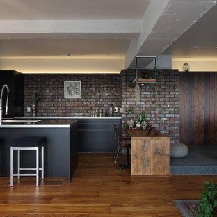 東京都下のアジアンスタイルのおしゃれなキッチン (シングルシンク、フラットパネル扉のキャビネット、黒いキャビネット、ステンレスカウンター、茶色いキッチンパネル、レンガのキッチンパネル、黒い調理設備、無垢フローリング、茶色い床) の写真