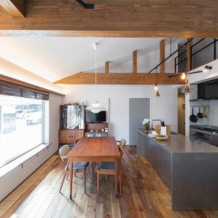 他の地域のインダストリアルスタイルのおしゃれなキッチン (オープンシェルフ、グレーのキャビネット、ステンレスカウンター、シルバーの調理設備の、無垢フローリング、茶色い床、グレーのキッチンカウンター) の写真