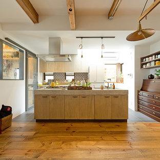 Design ideas for a galley open plan kitchen in Osaka with medium wood cabinets, terrazzo benchtops, grey splashback, porcelain splashback, dark hardwood floors, with island and brown floor.