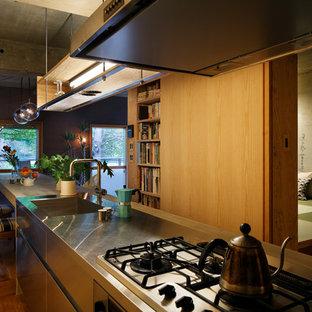 Immagine di una cucina etnica con lavello a vasca singola, ante lisce, ante in acciaio inossidabile, pavimento in legno massello medio, isola e pavimento marrone