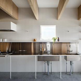 他の地域のインダストリアルスタイルのおしゃれなI型キッチン (一体型シンク、オープンシェルフ、コンクリートの床、ステンレスカウンター、メタリックのキッチンパネル、アイランドなし、白いキャビネット、シルバーの調理設備の) の写真
