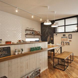 他の地域のビーチスタイルのおしゃれなキッチン (白いキッチンパネル、サブウェイタイルのキッチンパネル、無垢フローリング、茶色い床) の写真