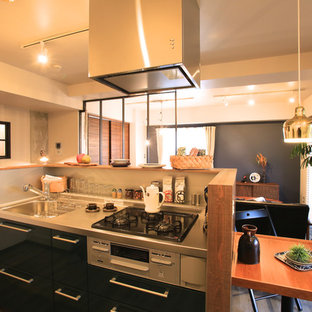Offene, Zweizeilige, Kleine Skandinavische Küche mit integriertem Waschbecken, flächenbündigen Schrankfronten, schwarzen Schränken, Edelstahl-Arbeitsplatte, Küchenrückwand in Weiß, gebeiztem Holzboden, Kücheninsel und grauem Boden in Sonstige