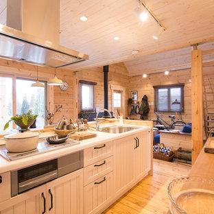 Skandinavische Küche mit Waschbecken, Schrankfronten mit vertiefter Füllung, weißen Schränken, braunem Holzboden und Kücheninsel in Tokio