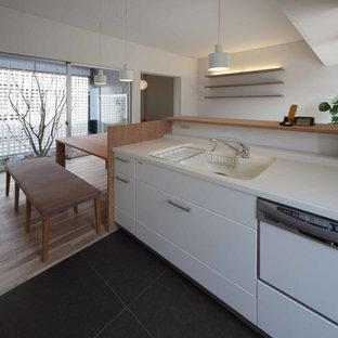 他の地域の小さい北欧スタイルのおしゃれなキッチン (白いキャビネット、人工大理石カウンター、セラミックタイルの床、茶色い床、白いキッチンカウンター) の写真