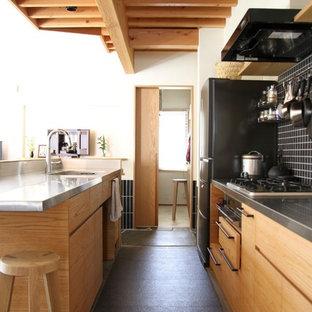 東京都下のコンテンポラリースタイルのおしゃれなキッチン (フラットパネル扉のキャビネット、中間色木目調キャビネット、ステンレスカウンター、黒いキッチンパネル、モザイクタイルのキッチンパネル、シルバーの調理設備、グレーの床) の写真