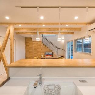 他の地域のアジアンスタイルのおしゃれなキッチン (一体型シンク、中間色木目調キャビネット、人工大理石カウンター、白いキッチンパネル、ガラス板のキッチンパネル、白い調理設備、合板フローリング、アイランドなし、白い床) の写真