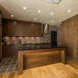 横浜のおしゃれなキッチン (ドロップインシンク、落し込みパネル扉のキャビネット、中間色木目調キャビネット、茶色いキッチンパネル、レンガのキッチンパネル、黒い調理設備、茶色い床、茶色いキッチンカウンター) の写真