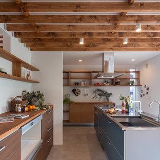 他の地域のコンテンポラリースタイルのおしゃれなキッチン (アンダーカウンターシンク、フラットパネル扉のキャビネット、中間色木目調キャビネット、ステンレスカウンター、シルバーの調理設備の) の写真