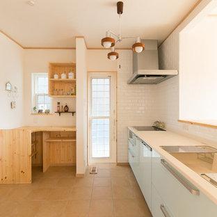 他の地域のアジアンスタイルのおしゃれなキッチン (一体型シンク、フラットパネル扉のキャビネット、テラコッタタイルの床、茶色い床、白いキッチンカウンター) の写真