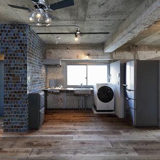 東京23区のインダストリアルスタイルのおしゃれなキッチン (一体型シンク、ステンレスカウンター、無垢フローリング、茶色い床) の写真
