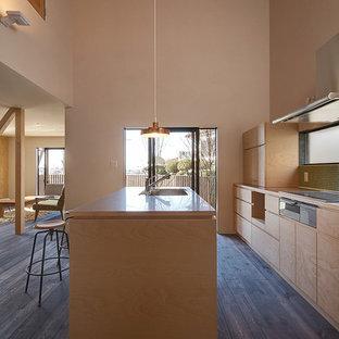 大阪の北欧スタイルのおしゃれなキッチン (シングルシンク、フラットパネル扉のキャビネット、淡色木目調キャビネット、緑のキッチンパネル、濃色無垢フローリング、茶色い床) の写真