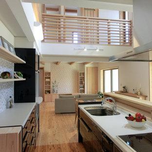 他の地域のモダンスタイルのおしゃれなキッチン (シングルシンク、フラットパネル扉のキャビネット、黒いキャビネット、無垢フローリング、茶色い床、黒いキッチンカウンター) の写真