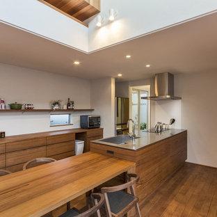 他の地域のコンテンポラリースタイルのおしゃれなキッチン (一体型シンク、フラットパネル扉のキャビネット、中間色木目調キャビネット、ステンレスカウンター、無垢フローリング、茶色い床、グレーのキッチンカウンター) の写真