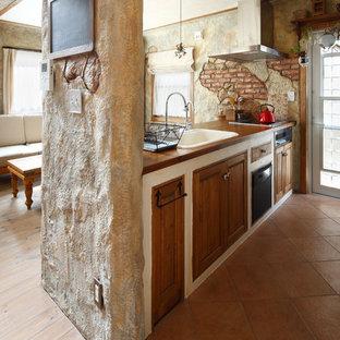 他の地域の地中海スタイルのおしゃれなキッチン (ドロップインシンク、落し込みパネル扉のキャビネット、中間色木目調キャビネット、木材カウンター、テラコッタタイルの床、茶色い床、茶色いキッチンカウンター) の写真